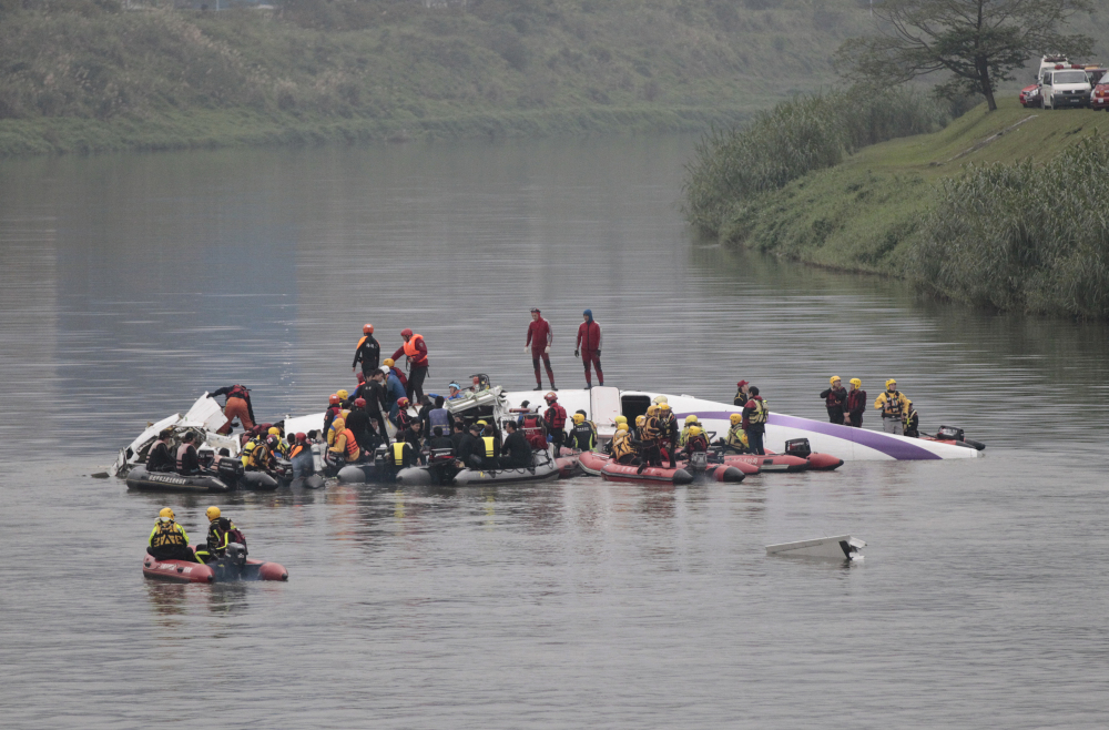 Emergency personnel try to extract passengers from a commercial plane after it crashed in Taipei, Taiwan, Wednesday.