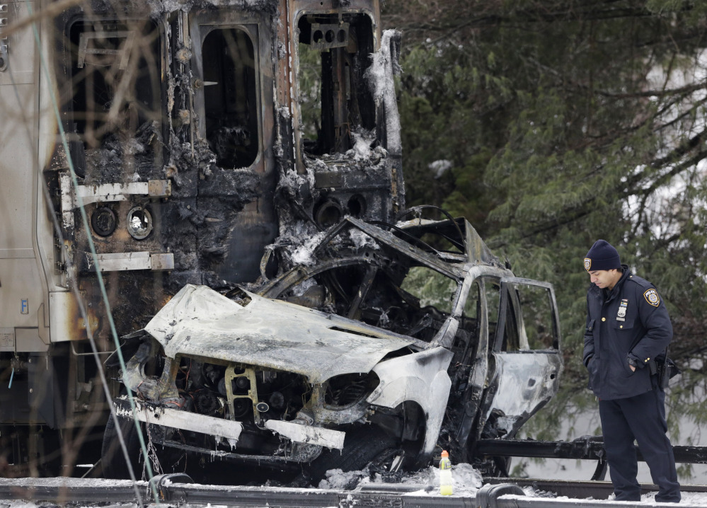 A police officer looks at an SUV that was crushed at the front of a Metro-North Railroad train, on Wednesday in Valhalla, N.Y.an)