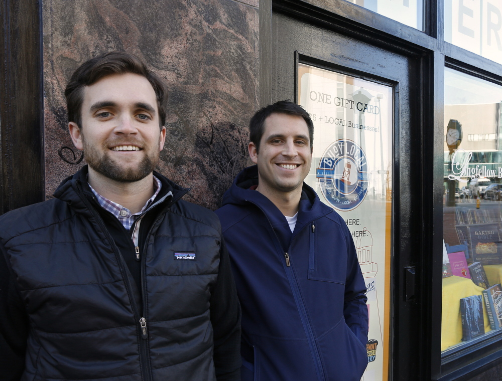 Sean Sullivan, left, and Kai Smith, co-founders of Buoy Local, stand outside Longfellow Books, which sells their gift cards.