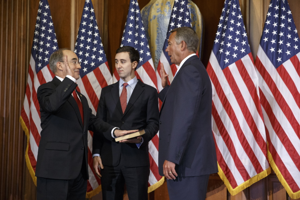 2nd District U.S. Rep. Bruce Poliquin, left, with his son Sam, center, is sworn in by House Speaker John Boehner on Jan. 6. Poliquin bucked his own party by voting against the most recent Republican proposal to repeal Obamacare.