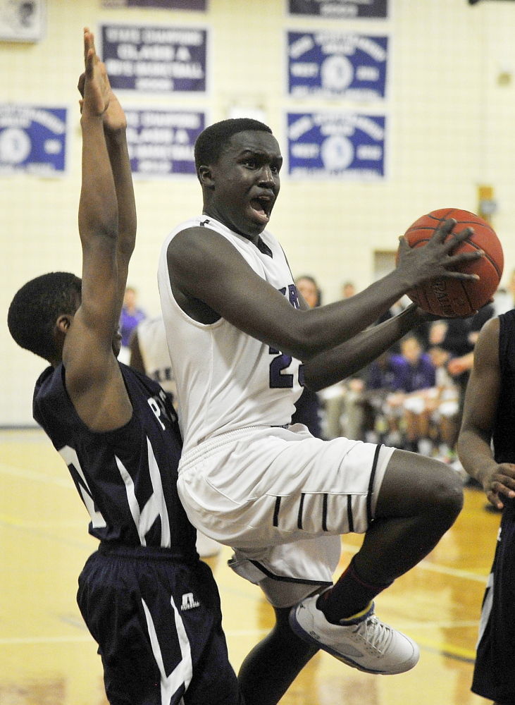 Deering's Moses Oreste splits a pair of Portland defenders on his way to the hoop Thursday night. The Rams end the regular season with a 12-6 record, while Portland enters the playoffs with a 16-2 record.