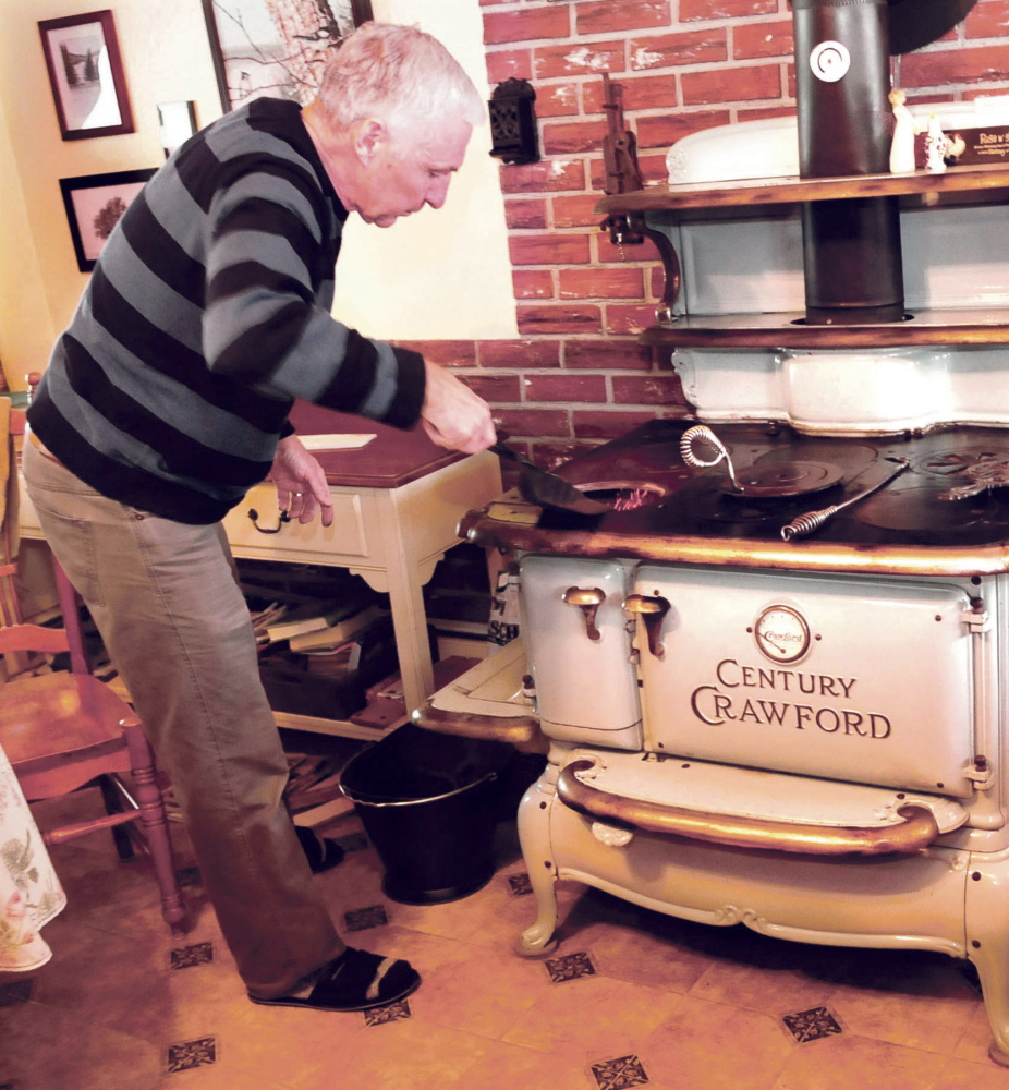 John Keister adds small pieces of nut coal into his stove at his Norridgewock home on Thursday. Keister says he learned how to use a coal stove from his grandfather, a descendant of Russian immigrants who settled in Pennsylvania.