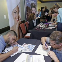 In this Wednesday, Oct. 22, 2014 photo, job seekers Stevens de la Pena, foreground left, and Eduardo Perez, foreground right, fill out a job application at a job fair in Miami Lakes, Fla. The Labor Department releases weekly jobless claims on Wednesday, Nov. 26, 2014. (AP Photo/Alan Diaz)