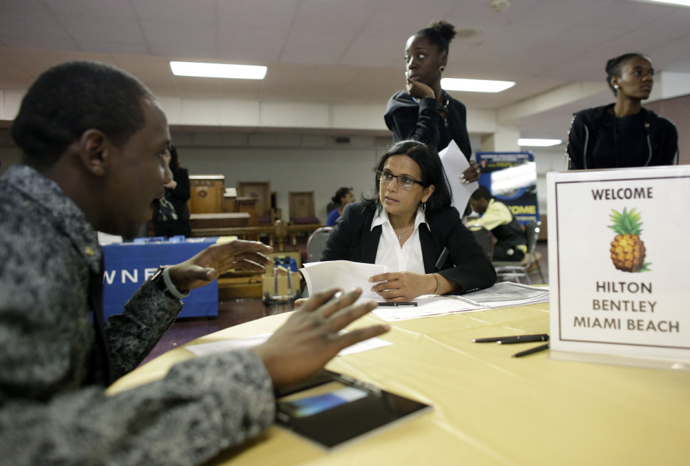 """At a job fair in Florida, an operations manager talks with a job seeker. Some businesses remain maddeningly slow to fill openings or describe """"skill mismatches."""""""