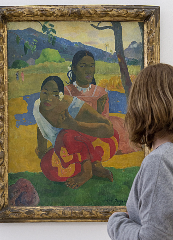 """A woman looks at """"Nafea faa ipoipo"""" (When will you merry?), a painting by Paul Gauguin that reportedly has been sold for $300 million."""