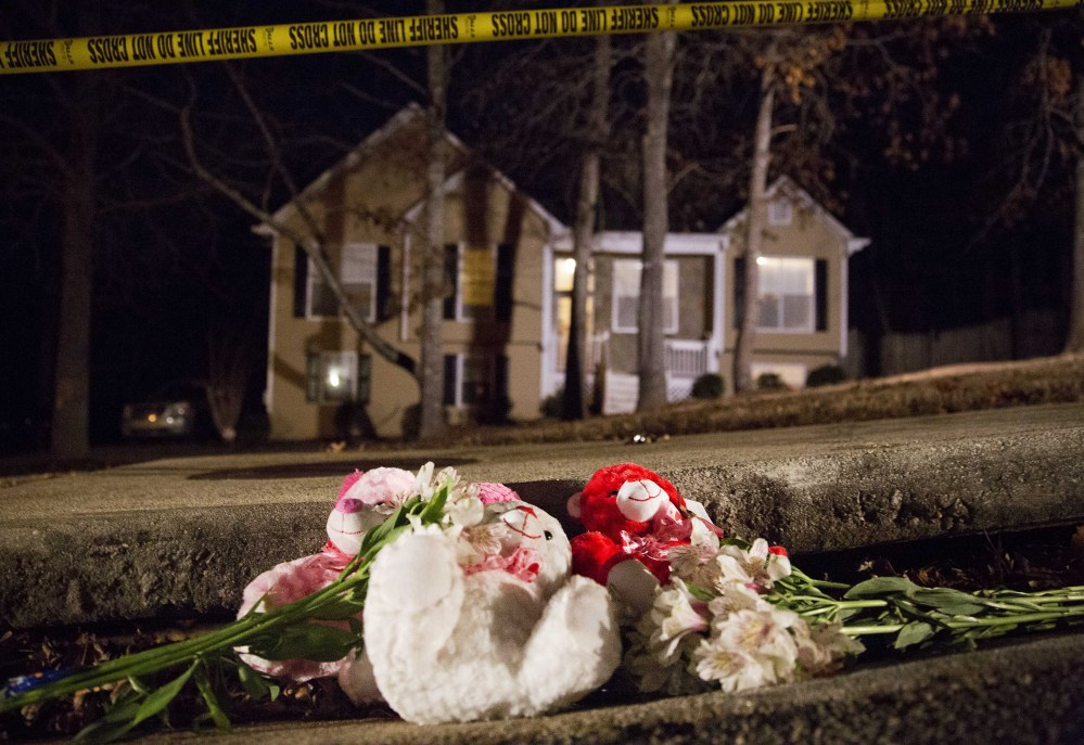 Flowers and teddy bears lay on the street outside the home of a shooting scene where authorities say five people are dead, including the gunman, in Douglasville, Ga. on Saturday.