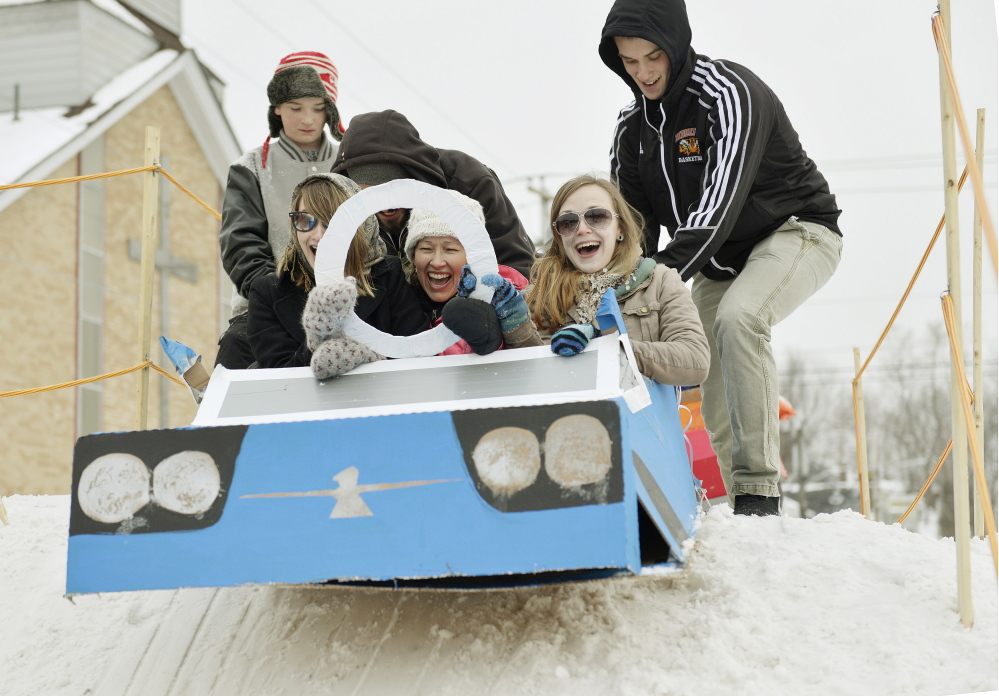 Biddeford's WinterFest featured a cardboard sled derby with runs on a man-made hill in the middle of downtown. That kid-again thrill of the downhill run registers on the faces of Tina Guay, left, Celeste Guay, center, and Kristy Holden of Biddeford as they get a push from the top of the Adams Street hill.