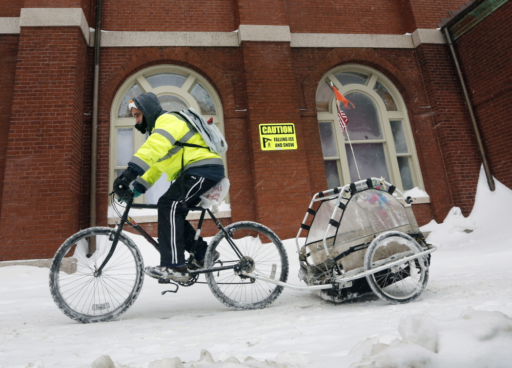 Gilbert Rosado of Portland rides past Sacred Heart Church on Mellen Street as the snow continues to fall on Sunday.