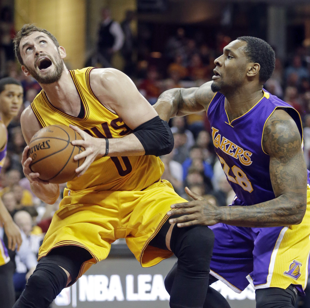 Cleveland's Kevin Love, left, makes a move to the hoop while being defended by the Lakers' Tarik Black on Sunday in Cleveland. Love scored 32 points and grabbed 10 rebounds to lift the Cavaliers to a 120-105 win.