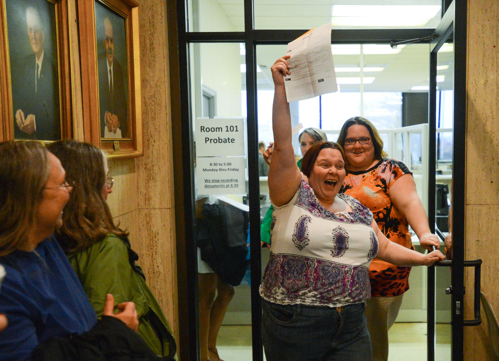 Eleanor Shue lifts her marriage license and yells in celebration as she and partner Jessica White emerge from the probate office after getting their marriage license in the Madison County Courthouse in Huntsville, Ala., on Monday.