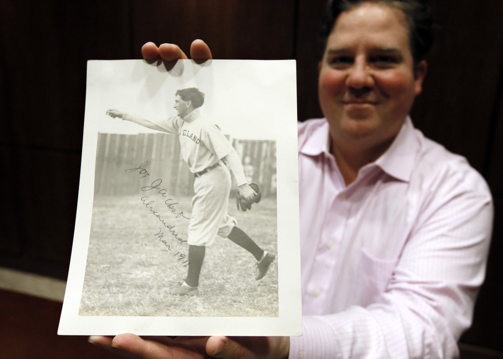 """Chris Ivy, director of sports auctions at Heritage Auctions in Dallas, holds a 1911 autographed photo of Cleveland ballplayer Joe Jackson. It may be the only autographed photo of """"Shoeless Joe."""""""
