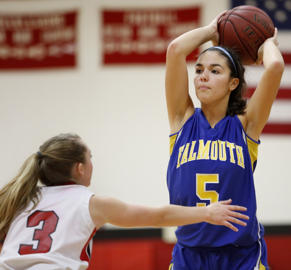 WELLS, ME - DECEMBER 11: Falmouth's Dayna Vasconcelos looks for a lane to pass the ball over Wells  defender Hannah Moody during a girls basketball game, Thursday, December 11, 2014.