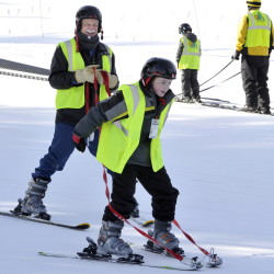 Jayden Gilpatrick takes one of his initial runs on skis, watched by teacher Dennis Woodruff, as he and other RSU 14 students with special needs hit the slopes recently at Shawnee Peak in Bridgton.