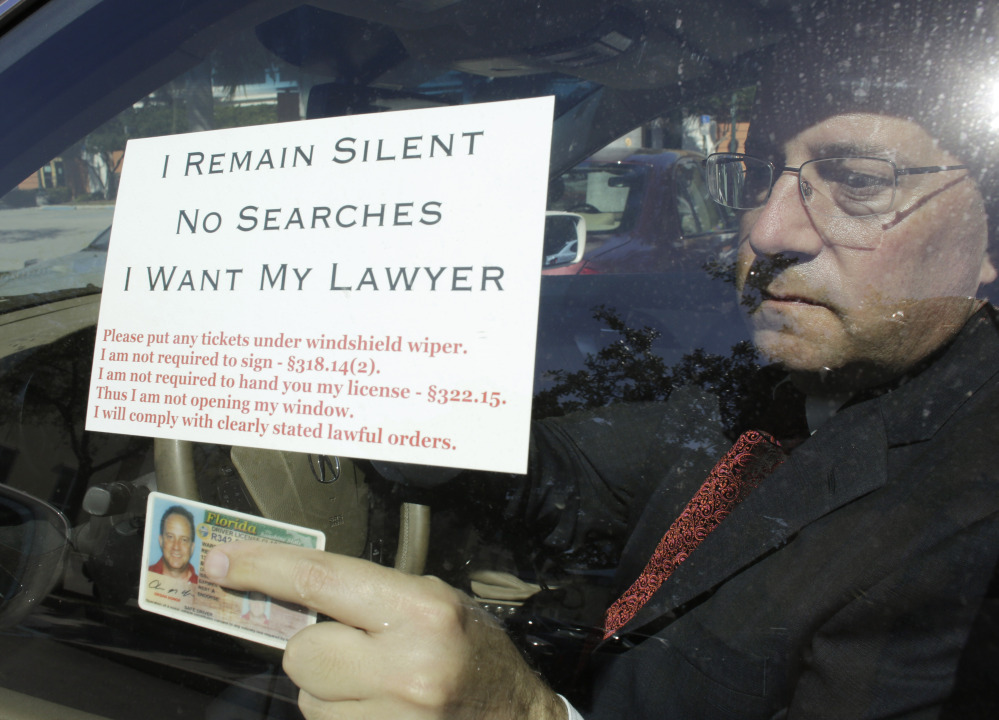 Florida attorney Warren Redlich displays a flier and his driver's license for a reporter. Redlich says his goal is to protect the wrongly accused, not drunk drivers.