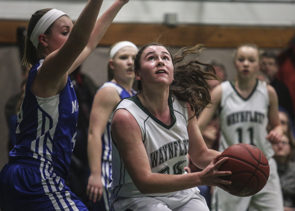 Ali Pope of Waynflete looks to shoot while defended by Erin Whalen of Madison, which will meet Boothbay Region in the quarterfinals at Augusta.