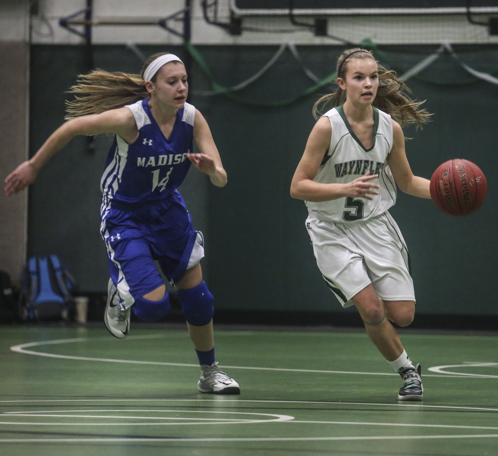 Izzy Burdick of Waynflete looks for room to drive Tuesday night against Sydney LeBlanc of Madison during Madison's 48-41 victory in a Western Class C prelim at Waynflete. Madison ended the game on a 14-4 run.