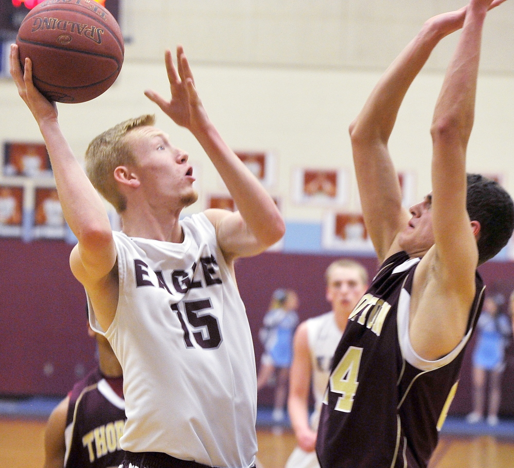 Windham's Ryan Gorman puts up a rebound over Thornton Academy's John Fogg. Gorman scored five points, including two clinching free throws late in the game.