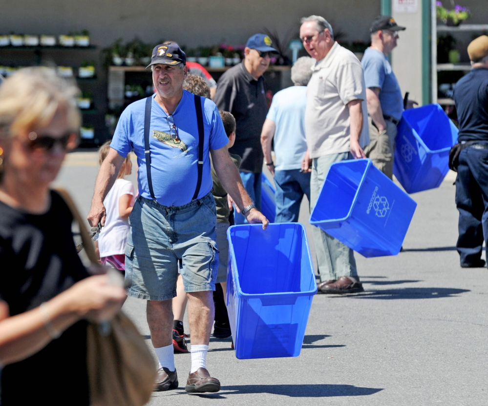 People return to their vehicles with free recycling bins from ecomaine at Elm Plaza in Waterville in June 2014. Ecomaine is proposing to work with Augusta on a pilot recycling program.