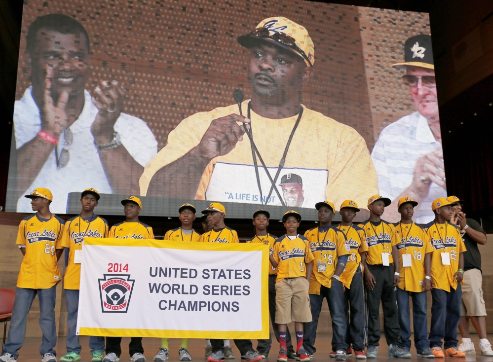 In this Aug. 27, 2014 file photo, members of the Jackie Robinson West All Stars Little League baseball team participate in a rally and listen to manager Darold Butler on the big screen as they celebrate the team's U.S. Little League Championship in Chicago.