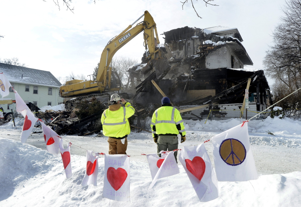 A crew works on demolishing the three-story apartment building at 20-24 Noyes St. in Portland last week, where a Nov. 1 fire killed six young adults. Prosecutors are still weeks away from deciding whether the landlord, Gregory Nisbet, should be charged.