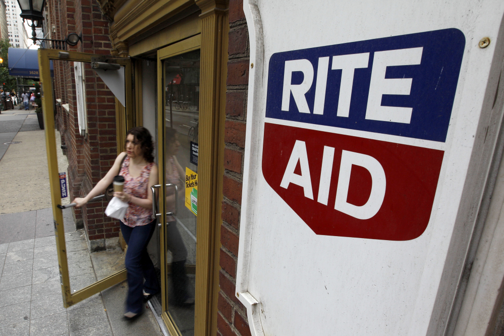In this June 20, 2011, file photo, a woman exits a Rite Aid store, in Philadelphia. Rite Aid, announced Wednesday, Feb. 11, 2015, it is expanding from running drugstores into managing pharmacy benefits with a planned, $2 billion purchase of EnvisionRx.