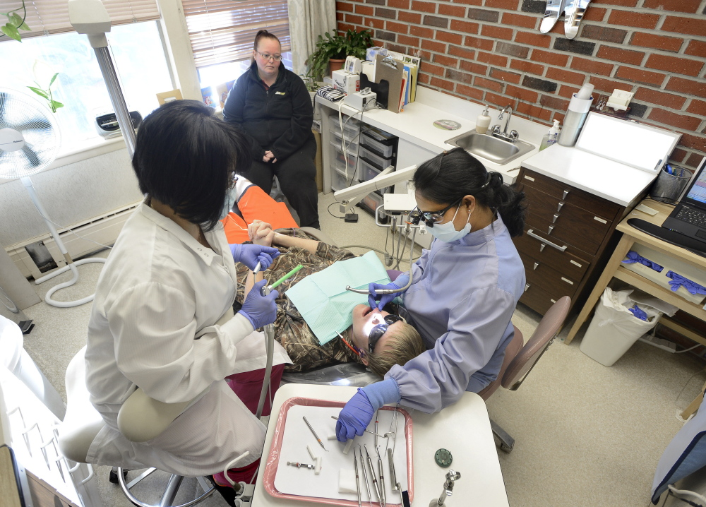 Alexzander Sprague, 14, is watched by his mother, Kelly Cousins of Buxton, as he gets a new filling from Dr. Vani Mallipeddi, right, and dental assistant Bich Ngoc Doan at Community Dental in Portland. Cousins, a mother of four, said she couldn't find a dentist near Buxton who would accept MaineCare patients.