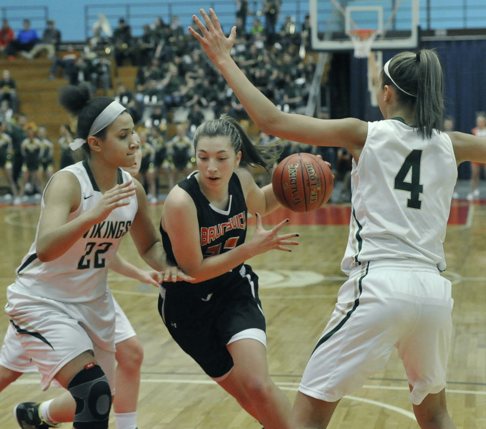 Adrianna White of Brunswick drives between Oxford Hills' Tiana Sugars, left, and Anna Winslow during an Eastern Class A quarterfinal Friday at the Augusta Civic Center. Brunswick advanced with a 37-32 win.