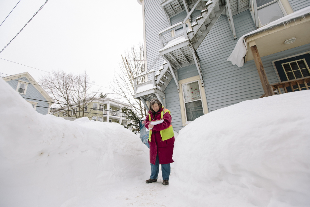 Field Inspections Coordinator Rhonda Zazzara makes a note of which part of the sidewalk at 61-65 Grant St. in Portland needs to be cleared of snow Thursday.