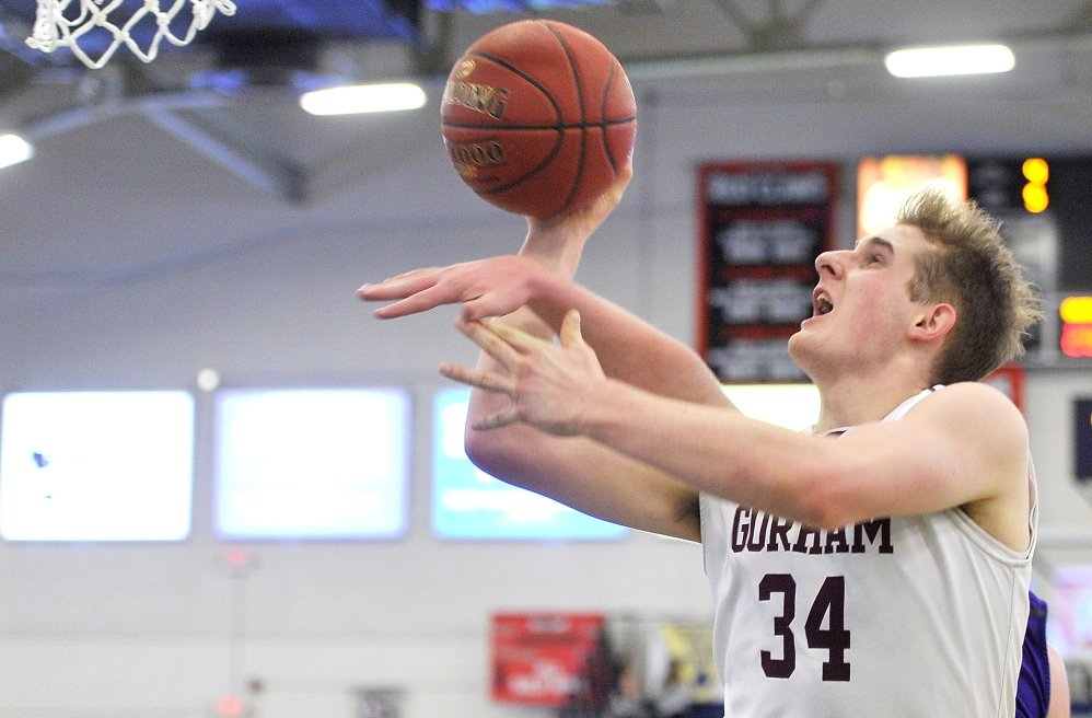Sam Kilborn of Gorham gets to the basket while avoiding an attempted block from a Deering defender. Kilborn finished with 13 points.