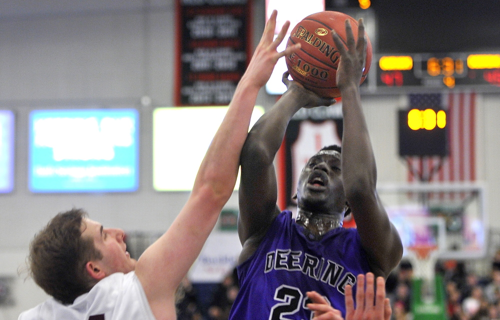 Garang Majok, who scored 10 points for Deering, lifts a shot over Sam Kilborn of Gorham during Deering's 61-59 victory Friday night in a Western Class A quarterfinal at the Portland Expo. Majok hit two late free throws that helped propel the Rams into a semifinal against Portland.