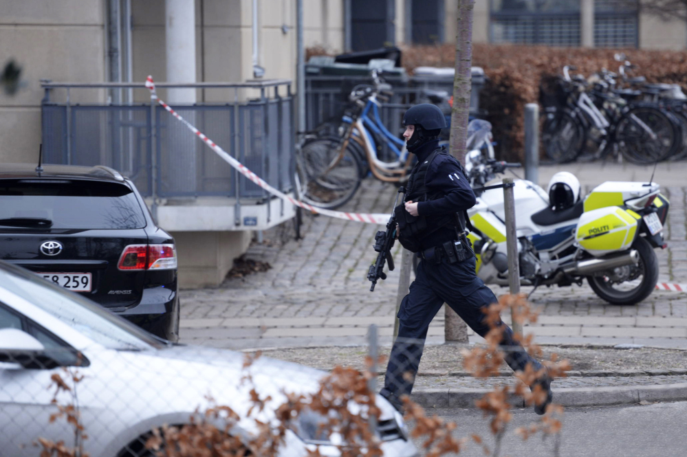 """An armed security officer runs down a street near a venue after shots were fired where an event titled  """"Art, blasphemy and the freedom of expression"""" was being held in Copenhagen on Saturday."""
