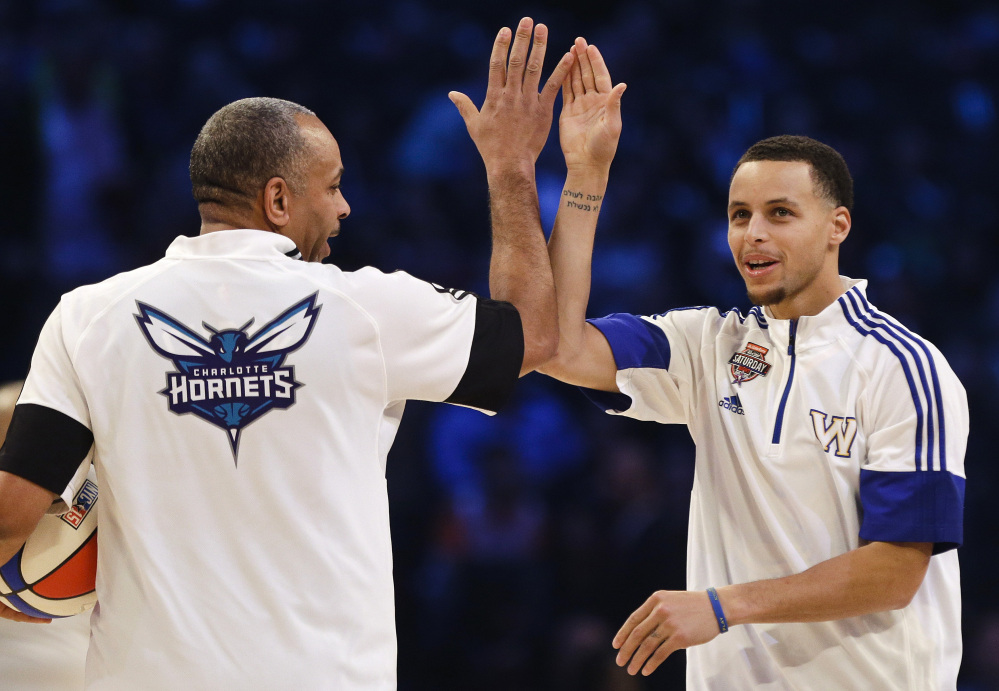 Golden State Warriors' Stephen Curry celebrates with his father, Dell Curry, left, during the NBA All-Star Saturday Shooting Stars event in New York.  Curry won the 3-point shooting contest.
