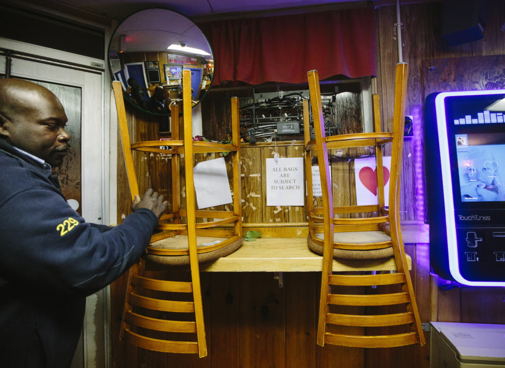 Doorman Emerson Boxill puts chairs up so the floor can be cleaned after Sangillo's last day on Saturday.