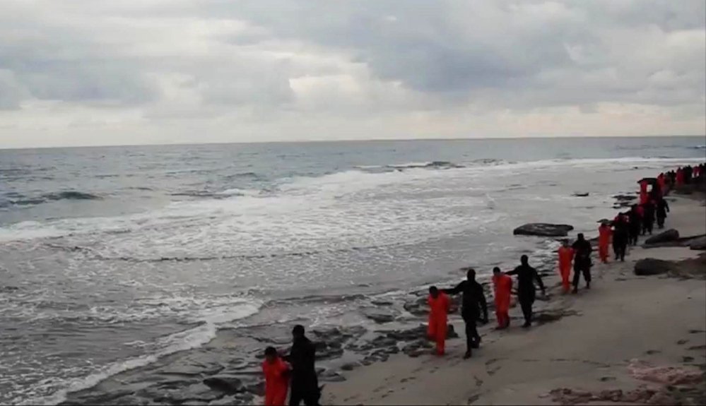 This image made from a video released Sunday by militants in Libya claiming loyalty to the Islamic State group purportedly shows Egyptian Coptic Christians in orange jumpsuits being led along a beach, each accompanied by a masked militant.