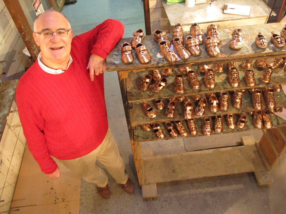 Robert Kaynes, CEO of American Bronzing Co., shows off some of the 100 pairs of baby shoes his company bronzes daily, down from 2,000 pairs in the '70s. But sales are climbing.