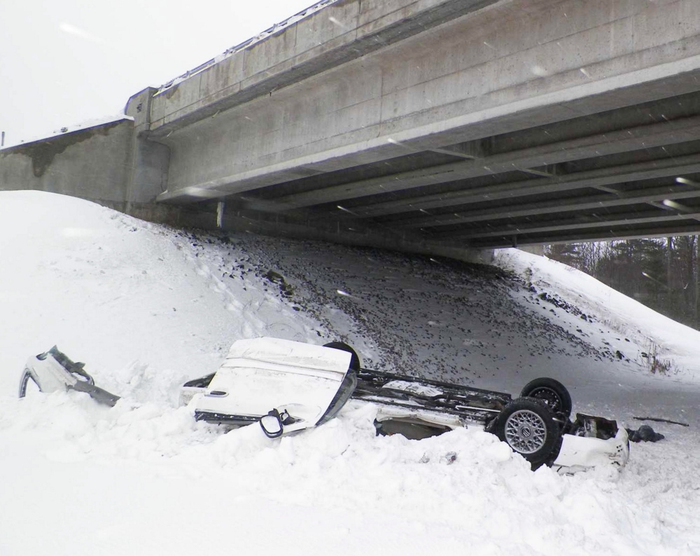 Car rests on its roof after the driver lost control and went over the top of a snowbank and off the bridge.