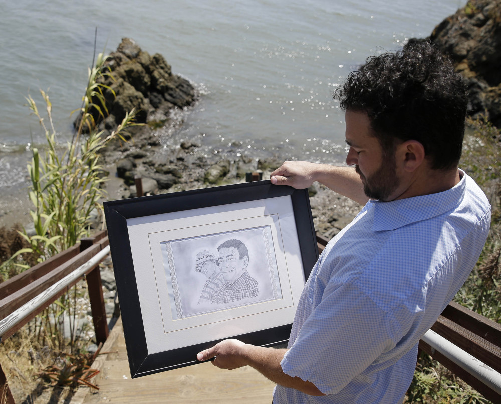 Dan Ager looks at a graphite sketch showing him and his father, Alan Ager, while walking toward a beach outside San Quentin State Prison in San Quentin, Calif. Alan Ager was killed in 2010 at Salinas Valley State Prison.