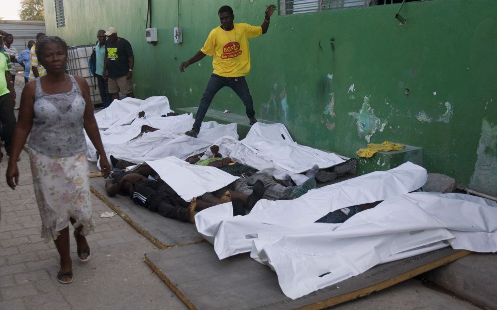 A woman walks away from bodies after failing to find a missing family member among them outside the morgue at the General Hospital in Port-au-Prince, Haiti, Tuesday.