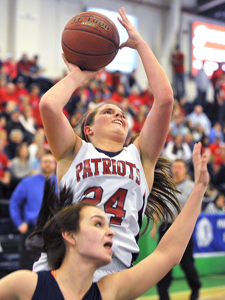 PORTLAND, ME - FEBRUARY 17: GNG #24, Maria Valente gets a shot off over the Poland defense as Gray-New Gloucester plays Poland in Class B West quarter-finals in the Maine High School Invitational Basketball Tournament at the Portland Expo. (Photo by Gordon Chibroski/Staff Photographer)