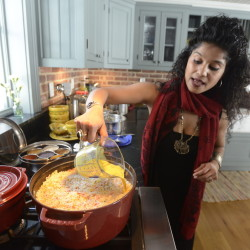 Cherie Scott pours saffron milk over rice for her lamb biryani at her home in Boothbay. The rice is cooked partway with cinnamon sticks, cloves, cardamom pods, cumin seeds and Turkish bay leaves.