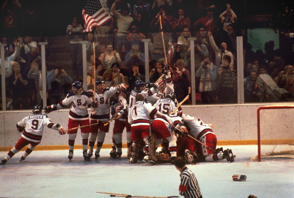 The U.S. hockey team pounces on goalie Jim Craig after a 4-3 victory against the Soviets in the 1980 Olympics, as a flag waves from the partisan Lake Placid, N.Y., crowd.