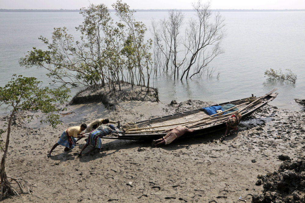 In this Feb. 1, 2015, photo, villagers help fishermen  push their boat to the water at Satyanarayanpur village in the Sundarbans, India.