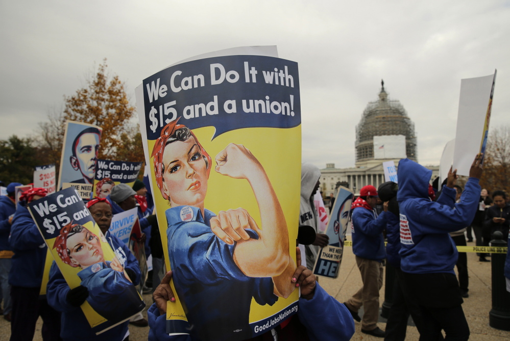People rally for a higher minimum wage in Washington in November.  But raising the minimum wage is turning out to be only a slight help for lowest-paid workers.