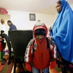 Fadumo Libah helps her son Hudeyfa, 5, dress for the cold weather as Somali immigrant Muhidin Libah, left, helps their other children get ready for school in Lewiston. Muhidin Libah has lived in Maine for nearly a decade and is still wary of winter weather, but his six children love the snow.