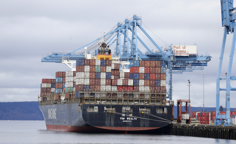 A cargo container ship sits docked at the Port of Tacoma, Washington, on Friday. With ships and their cargo weeks behind schedule, dockworkers and their employers reached a tentative agreement on a new contract late Friday.