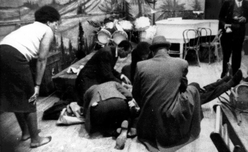 In this Feb. 21, 1965, file photo, Malcolm X is tended to as he lies fatally wounded on the stage of the Audubon Ballroom in the Harlem section of New York after being shot multiple times.