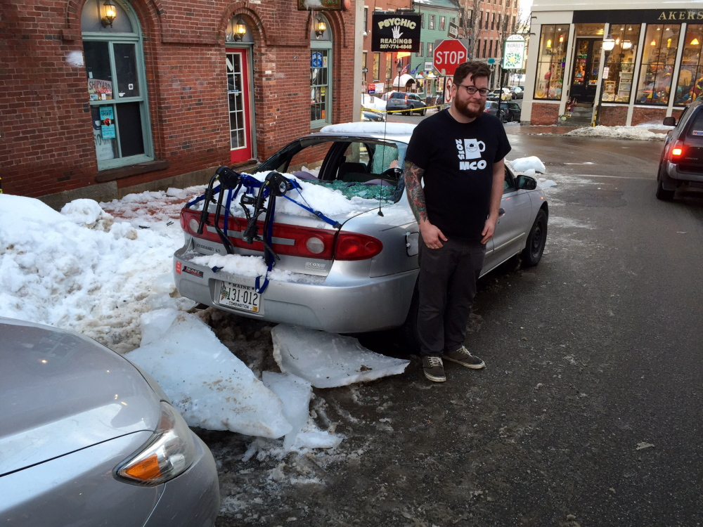 Adam Sousa stands by his car after it was hit by ice that fell off a building on Exchange Street. Dennis Hoey/Staff Writer