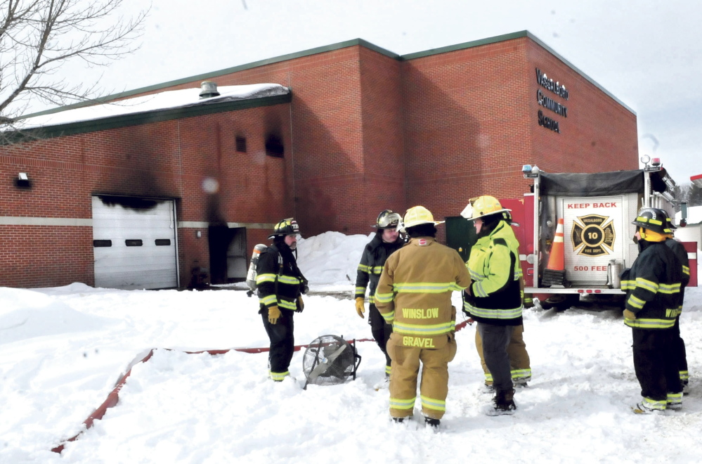 Firefighters from Vassalboro and Winslow wait as the Vassalboro Community School is ventilated of black smoke after a tractor caught on fire inside the attached garage, causing substantial damage on Sunday.