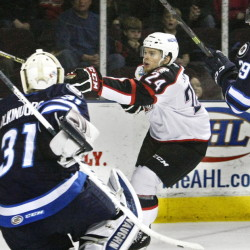 Pirates center Brendan Shinnimin, center, tries to control a wild puck in front of IceCaps goalie Jussi Olkinuora with defensive pressure from Jordan Hill on Sunday.
