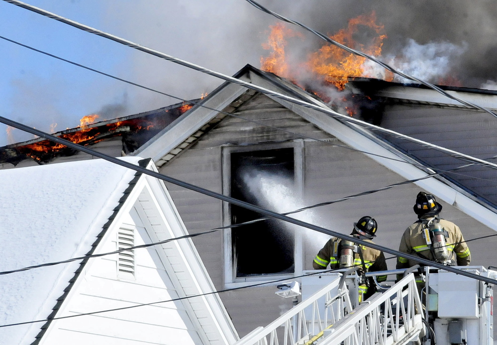Firefighters spray water into the third-floor window as flames break through the roof of an apartment building on Paris Street in Waterville on Monday.